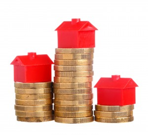 Red small house on top of stacks of coins isolated on white background.